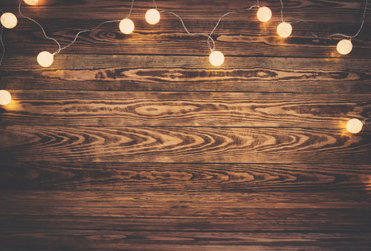 Old wooden planks with christmas decoration. Brown background with lightbulbs