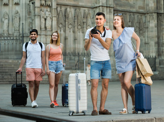 Young cheerful woman and man tourists are holding camera in hands and photographing