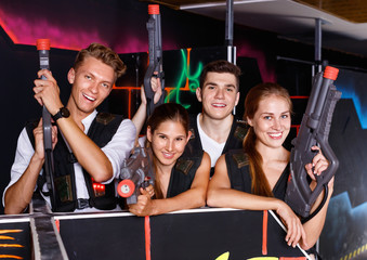 Group portrait of joyful young people with laser guns in their hands in room for playing laser tag