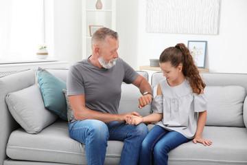 Senior man checking little girl's pulse indoors