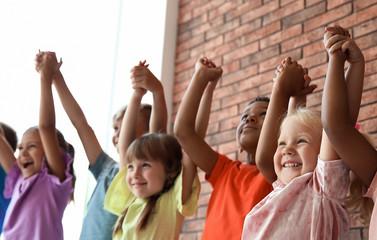 Little children holding hands together indoors. Unity concept Fotoväggar