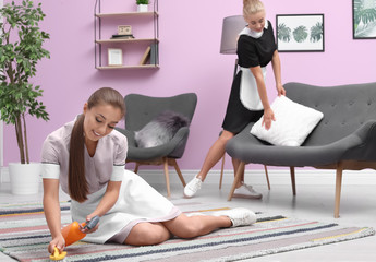 Young chambermaid cleaning carpet in living room