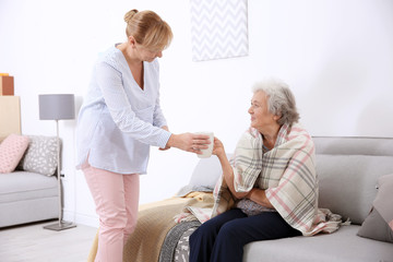 Caregiver giving cup of tea to senior woman at home