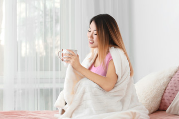 Beautiful smiling Asian woman with cup of tea at home