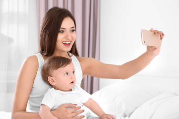 Happy young mother with her cute little baby taking selfie in bedroom