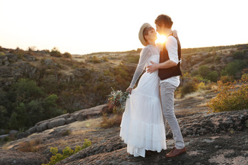 Happy newlyweds with beautiful field bouquet standing on rock at sunset