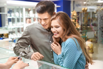 Young couple choosing earrings in jewelry store