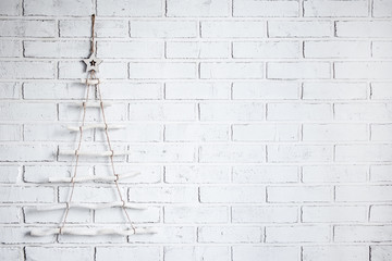 wooden chrtistmas tree decoration over white brick wall with copy space
