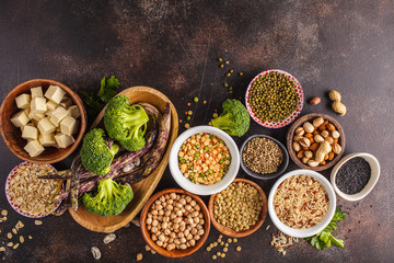 Vegan protein source. Tofu, beans, chickpeas, nuts and seeds on a dark background, top view, copy space.