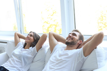 Smiling beautiful couple sitting on a sofa and dreaming about new home.