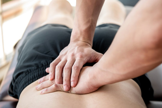 Therapist giving lower back sports massage to athlete male patient