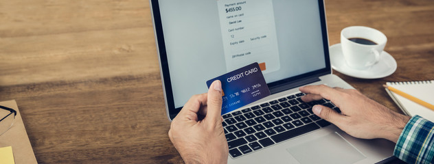 Hand of a man holding credit card making payment online with laptop computer