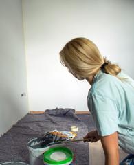 Renovierungskonzept: Junge Frau rührt mit Pinsel im Farbtopf