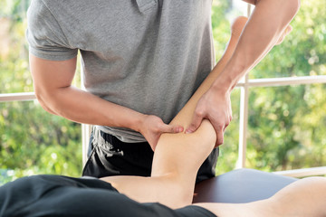 Male therapist giving leg and calf massage to athlete patient in clinic
