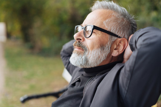 älterer mann sitzt entspannt im park