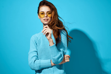 woman in blue sweater in yellow glasses on blue background