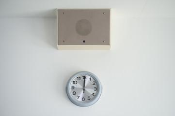 教室の溶暗場所、12時を指す時計と放送スピーカー