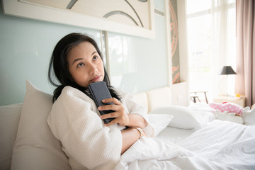 Woman sitting on white bed looking smartphone with stress or worrying