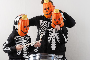 Happy friendly family of musicians in carnival costumes, boys and young mother play drum and try to sing with microphone. Black suit with image of skeletons. Classic halloween costume. Funny children