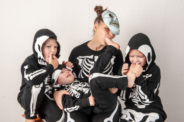 Happy children in carnival costumes, boys with his mother. Black suit with the image of skeletons. Classic Halloween costume. Happy childhood of children