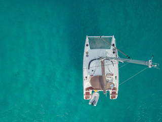 Aerial bird's eye view drone of boat docked in mediterranean tropical beach with turquoise - sapphire waters