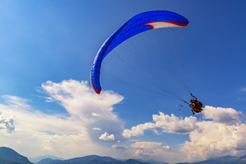 Foto op Aluminium Luchtsport 2018-08-23, Saint-Vincent-les-Forts, France. Tandem paragliders fly with beautiful clouds on the background.