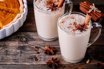 Homemade Chai Tea Latte with anise and cinnamon stick in glass mugs with pumpkin pie