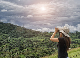 Woman traveler take photo view of green mountain with her camera on holiday