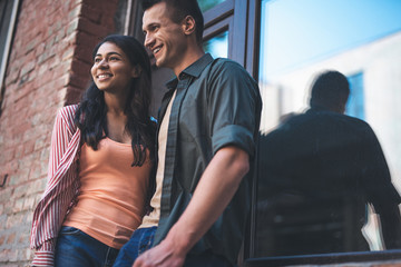 Couple smiling. Cheerful relaxed young couple standing outdoors next to the window and looking into the distance with a smile