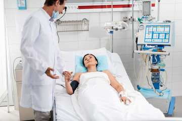 You are healthy. Portrait of smiling surgeon in white lab coat touching arm of woman. Lady lying in hospital bed and looking at man with expression of relief