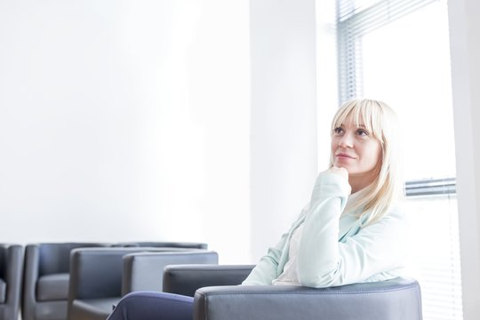 Pensive mid adult woman sitting in doctor's waiting room wit