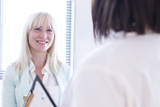 Female patient listening to doctor and smiling