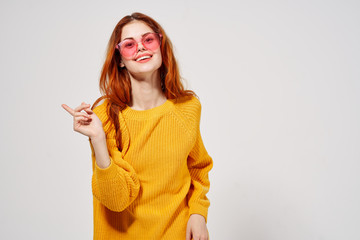 happy woman in glasses and yellow sweater shows Finger to the side