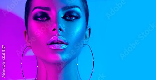 Wall mural Fashion model brunette woman in colorful bright neon lights posing in studio. Beautiful sexy girl, trendy glowing makeup, metallic silver lips