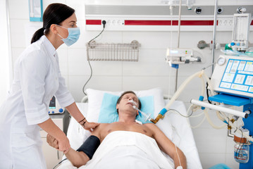 Young female doctor in protective face mask touching hand and shoulder of patient while looking at monitor of breathing machine. Man lying in hospital bed with endotracheal tube in the mouth
