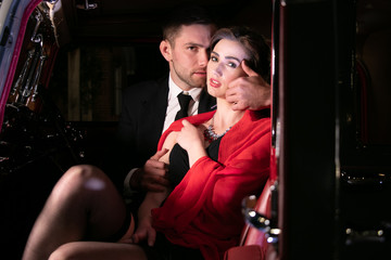 Good looking sexy couple, handsome man in suit, beautiful woman in red dress, embrace passionately in vintage car