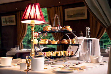 vintage afternoon tea stand through window of train compartment
