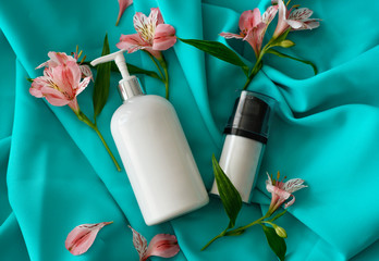 SPA composition. Set of blank cosmetic bottles and tubes on green background.