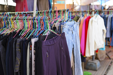 Pants and jeans on hangers in the second hand store