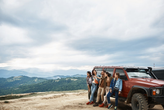 Pleasant happy young friends standing near their car while enjoying view from the mountain hill