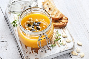 Pumpkin soup with pumpkin seeds topping in glass jar overhead rustic wooden table