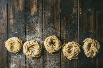 Variety of italian homemade raw uncooked pasta spaghetti and tagliatelle in row with semolina flour over dark plank texture wooden table. Flat lay, copy space