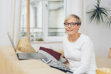 Woman sat at home with open laptop on sofa