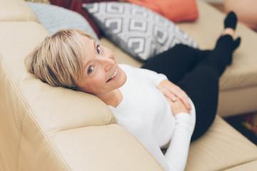 lächelnde frau sitzt auf der couch und schaut nach oben