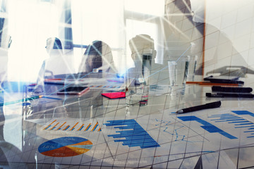 Silhouette of young workers in the office with statistic worksheets. concept of teamwork and business. double exposure
