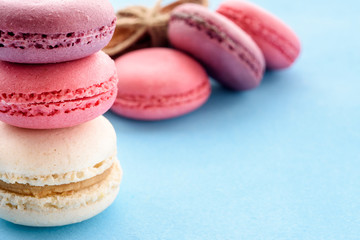 French Macarons on a blue background. Trendy dessert. Sweet cakes.