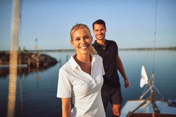 Smiling young woman standing with her husband on their yacht Wall mural