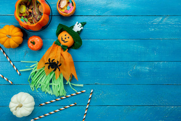 Table top view aerial image of decoration Happy Halloween day background concept.Flat lay accessories essential object to party the pumpkin  & cute doll on blue wooden.Space for creative design.