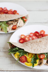 Healthy whole wheat wrap with chicken breast, mushroom, cherry tomatoes, bell pepper, parsley and arugula leaves. Healthy and balanced snack