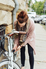 Young woman chaining her bike to a bar